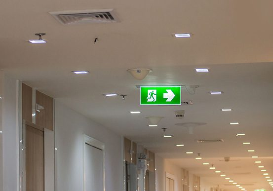 FIRE & SECURITY SYSTEMS green emergency exit sign in hospital showing the way to escape