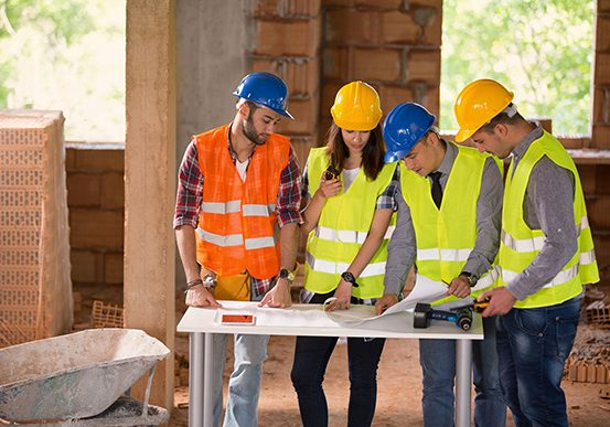 Principle Contractor Engineers at construction site studying blue print